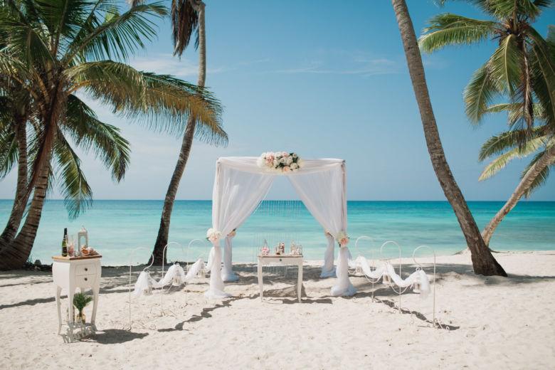 Белая арка с розовыми пионами и навесом. Крючки с фонариками и жемчугом. Стол круглый с белой тканью – WedDesign | Свадьба в Доминикане